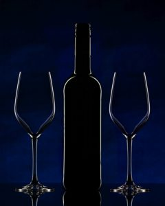 Red wine bottle and empty glasses on blue background