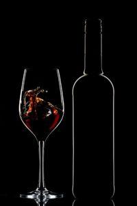 Red wine bottle and splashing wine in glass on dark background