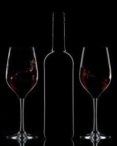 Red wine bottle and splashing wine in glasses on dark background