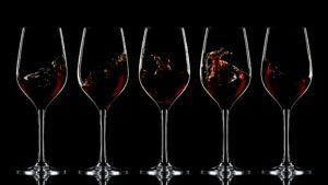 Splashing red wine in glasses on dark background