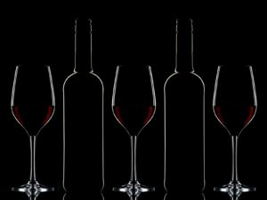 Red wine bottles and red wine in glasses on dark background