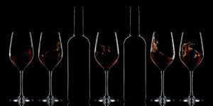 Red wine bottles and splashing red wine in glasses on dark background
