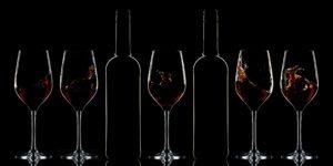 Red wine bottles and splashing red wine in glasses on dark background